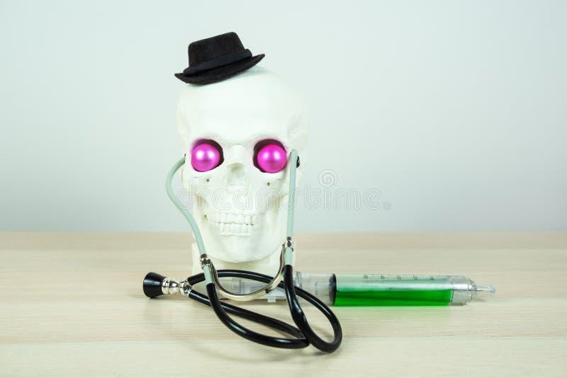 Скульптура черепа нося черную элегантную шляпу, stratoscopes, с большим медицинским шприцем и яркими розовыми глазами пародийност стоковые изображения