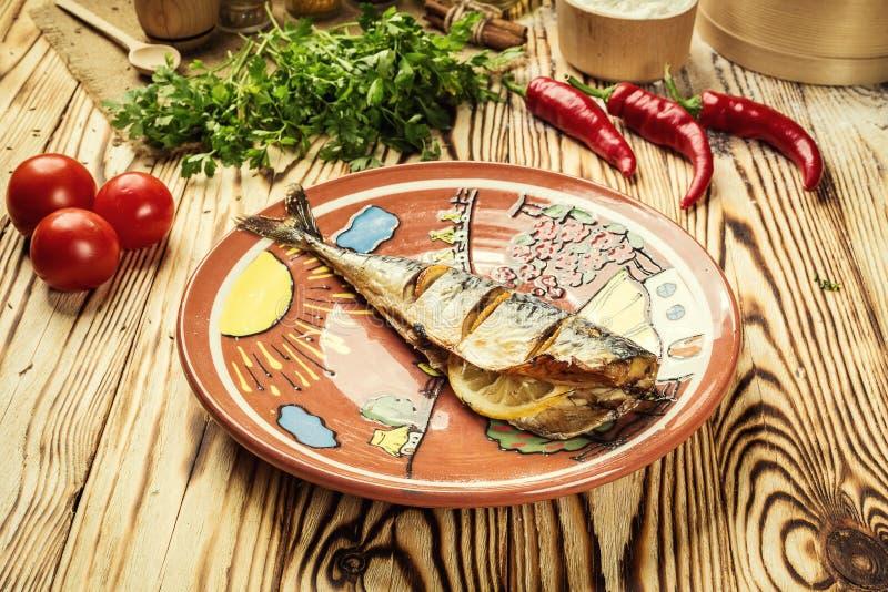 Скумбрия испекла с лимоном на плите, чесноке, испеченной рыбе, всем bak стоковые изображения rf