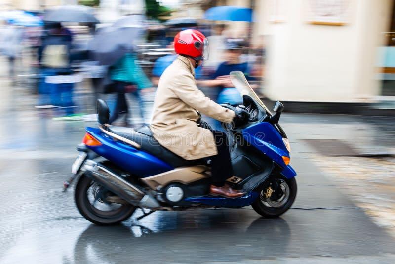 Скутер в нерезкости движения на влажной улице города стоковое изображение rf