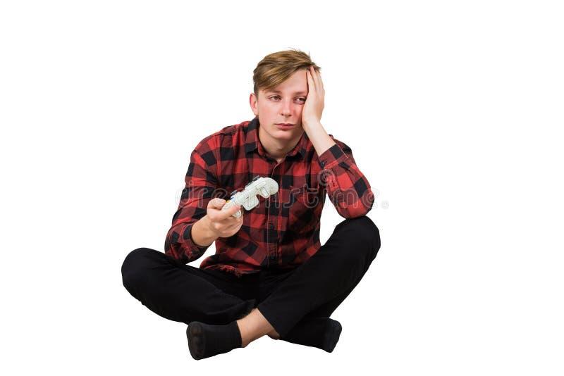 Скучный юноша сидит на полу и играет в видеоигры, изолированные на белом фоне Спящий мальчик держит джойстик, стоковая фотография