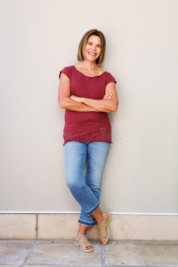 Склонность более старой женщины полного тела счастливая против стены стоковые изображения rf