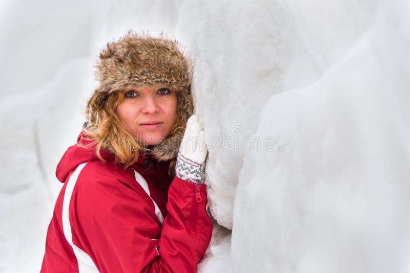 Склонность девушки на стене снега стоковое изображение rf