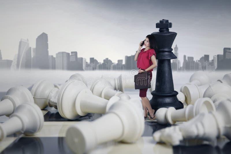 Склонность коммерсантки на ферзе шахмат стоковое изображение rf