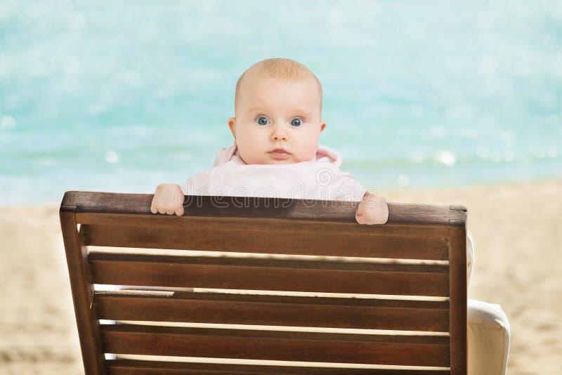 Склонность младенца на Deckchair на пляже стоковое изображение rf
