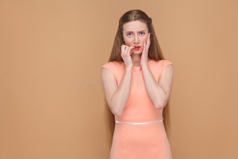 Слабонервная несчастная confused девушка смотря ногти камеры и укуса стоковое изображение