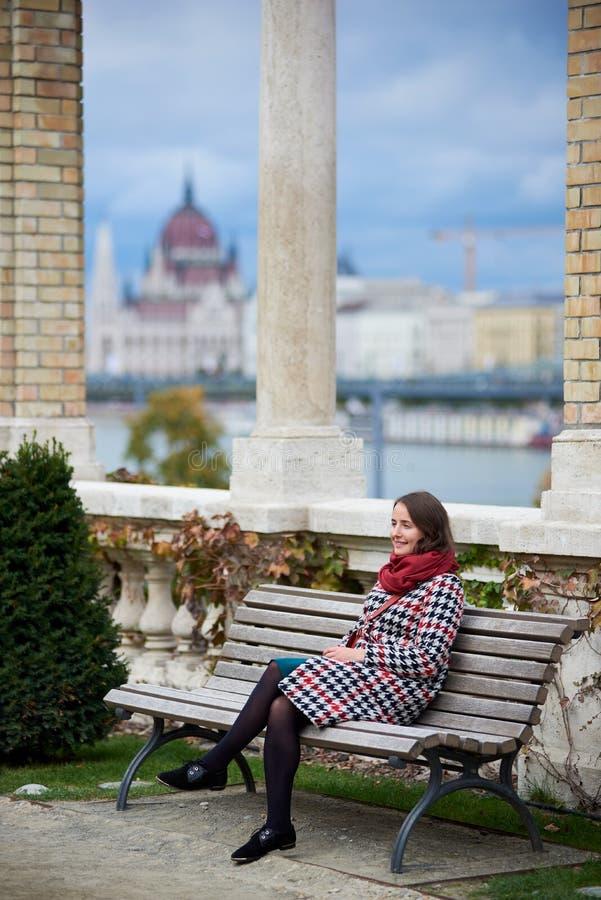 Славная девушка сидит самостоятельно на стенде около столбцов стоковые изображения