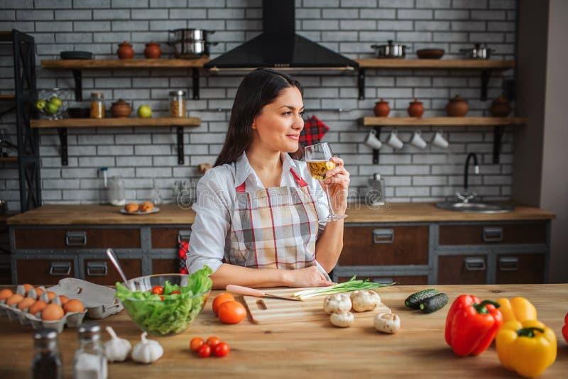 Славная женщина наслаждается выпить вино в кухне на таблице Она смотрят, что выпрямляет и усмехает Красочные овощи на таблице стоковые фотографии rf