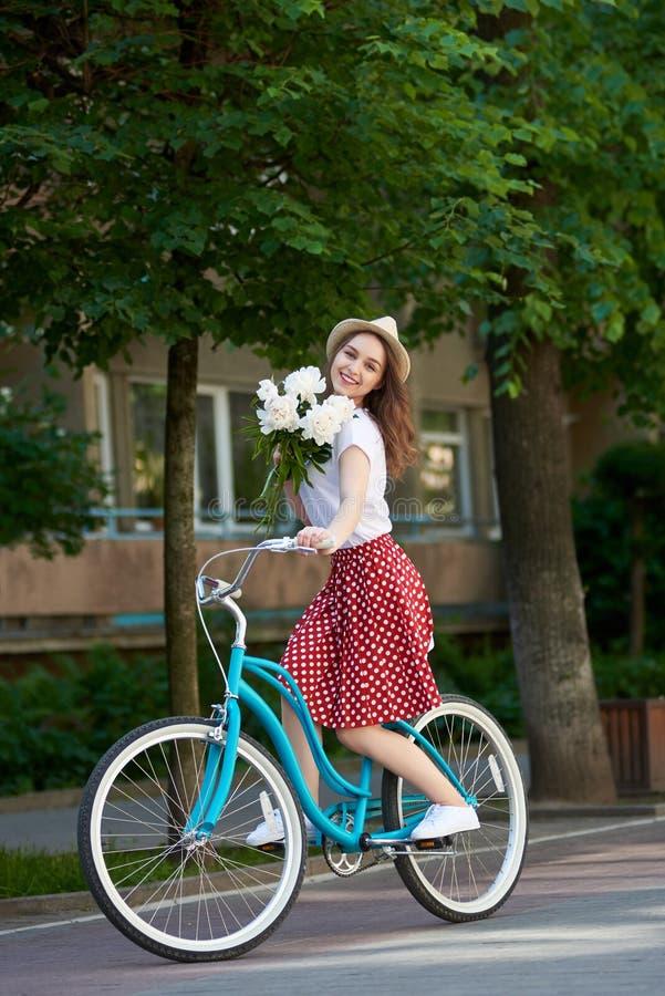 Славная женщина на ретро велосипеде с пионами едет вперед стоковое фото