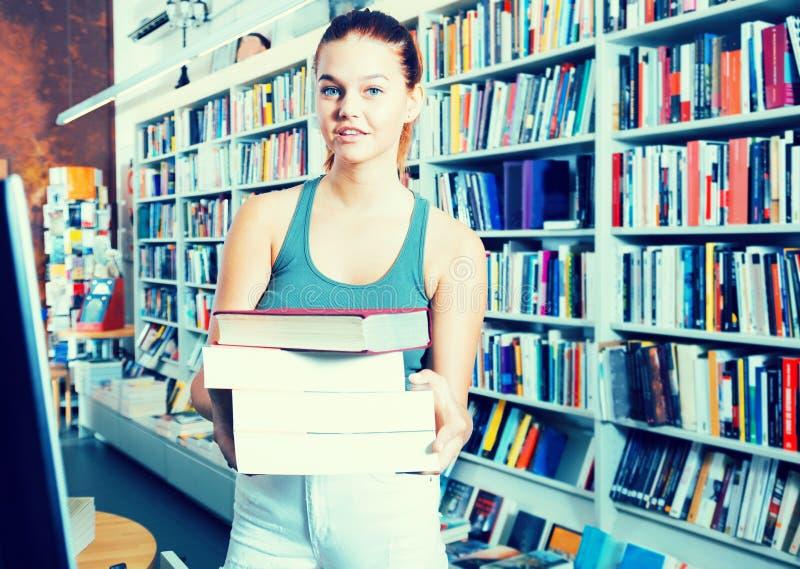 Славная женщина предлагает книгу в bookstore стоковые фотографии rf