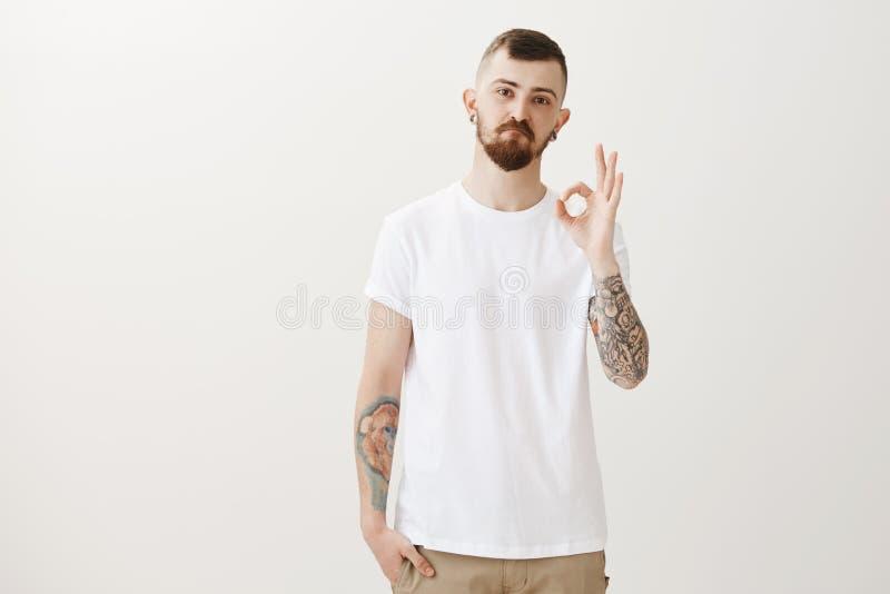 Славная идея, человек, как она Гордый удовлетворенный красивый парень с справедливыми волосами, татуировки и показ бороды ok или  стоковая фотография rf