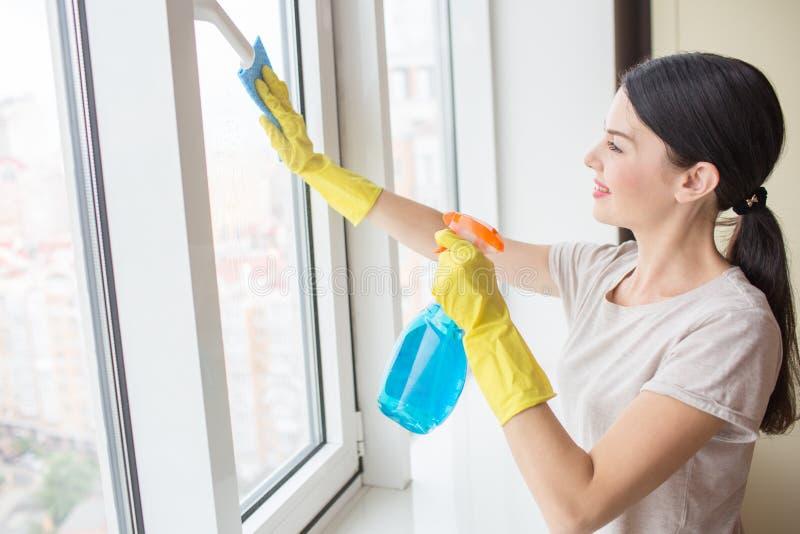 Славная и восхитительная девушка стоит перед окном и очищать ее с ветошью и голубым жидкостным брызгом Девушка носит желтый цвет стоковое изображение rf