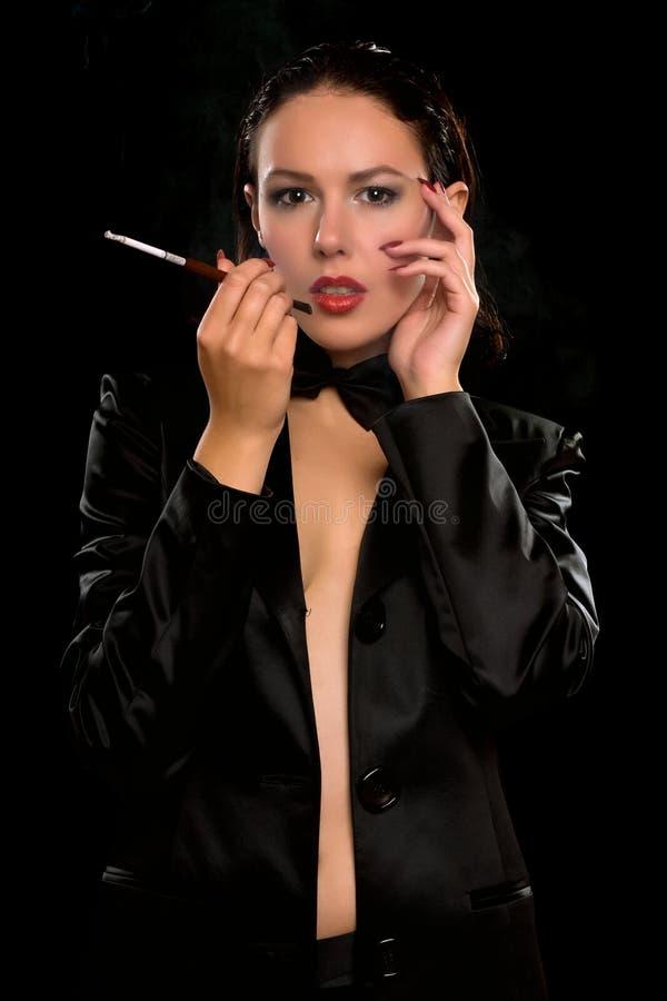 Славная молодая женщина с сигаретой изолировано стоковая фотография