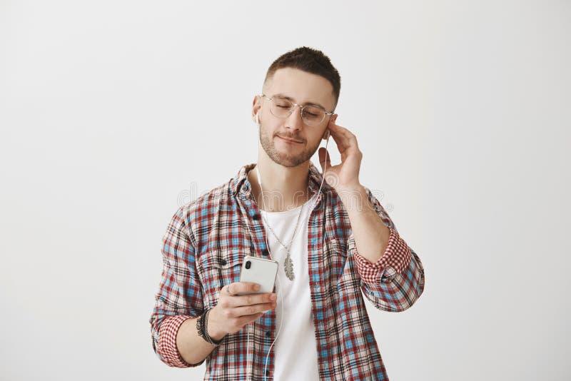 Славная музыка портальна к новому миру Привлекательный стильный музыкант в стеклах держа smartphone и нося наушники пока стоковое фото rf