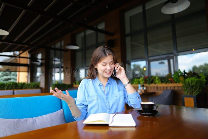 Славная студентка отдыхая на кафе с тетрадью и чашкой кофе, говоря смартфоном стоковые фотографии rf