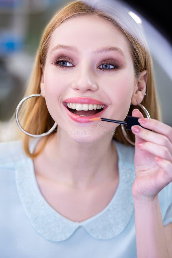 Славное использование молодой женщины сияющие lipgloss стоковые фото
