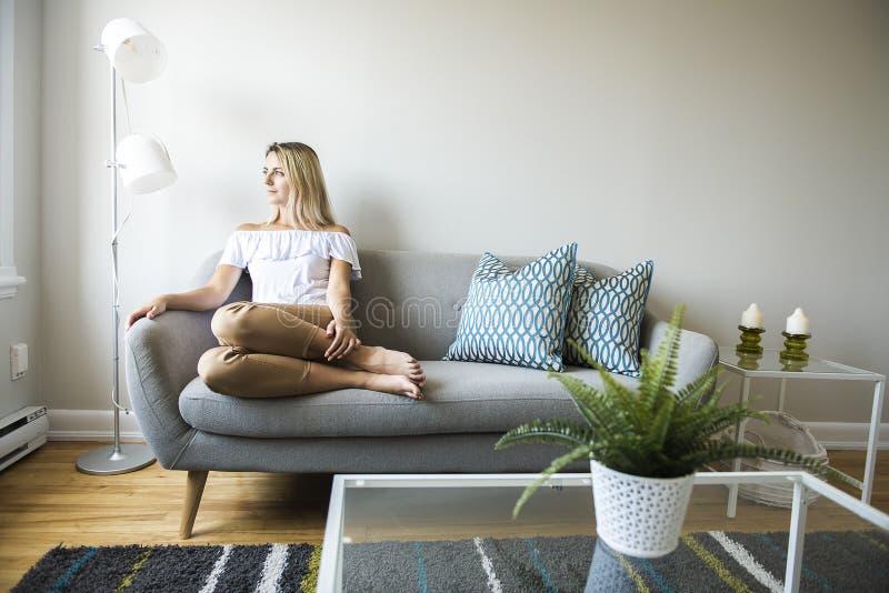 Славные белокурые женщины сидят на софе дома стоковые изображения