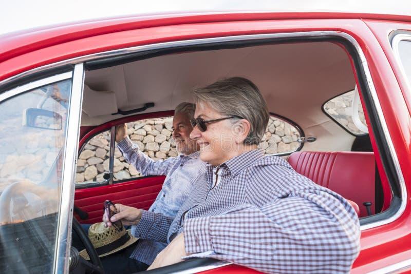 Славные взрослые объятие и любовь пар внутри красного старого винтажного автомобиля припаркованного на дороге улыбки и иметь поте стоковые фото