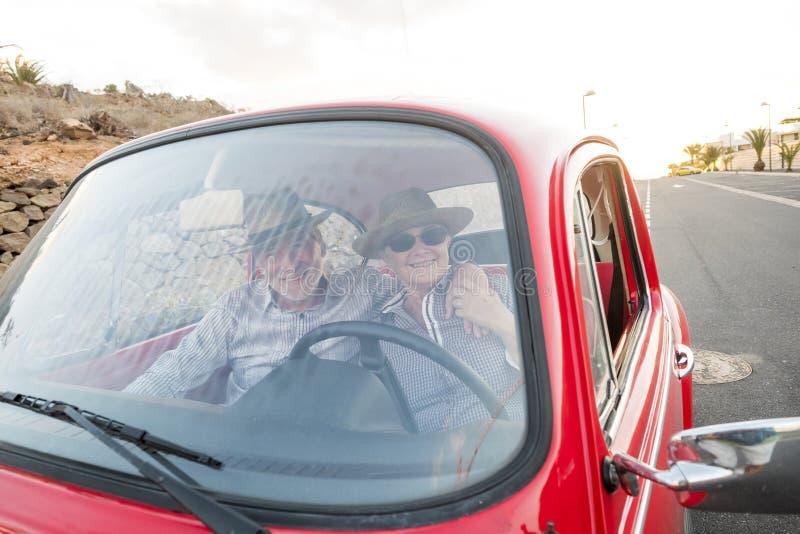 Славные взрослые объятие и любовь пар внутри красного старого винтажного автомобиля припаркованного на дороге улыбки и иметь поте стоковые изображения rf