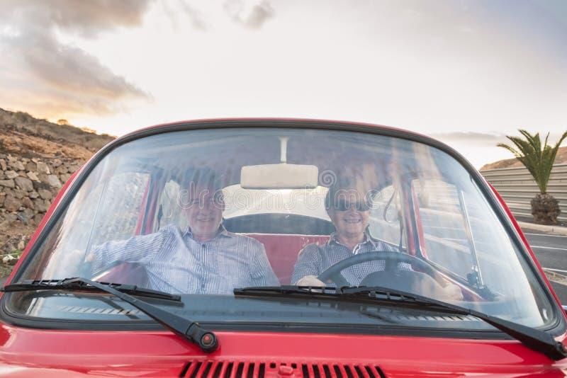 Славные взрослые привод и любовь пар внутри красного старого винтажного автомобиля припаркованного на дороге улыбки и иметь потех стоковые фото