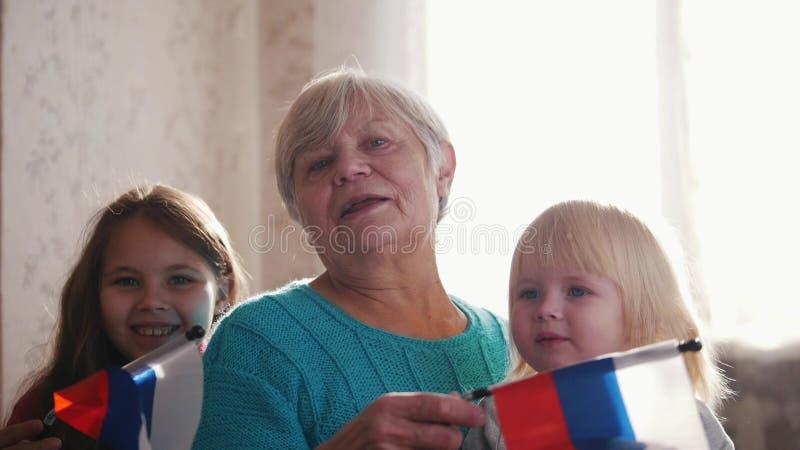 Славные девушки и их бабушка наслаждаются солнечным утром Полезного время работы дома Флаг России в руках бабушки стоковые изображения rf