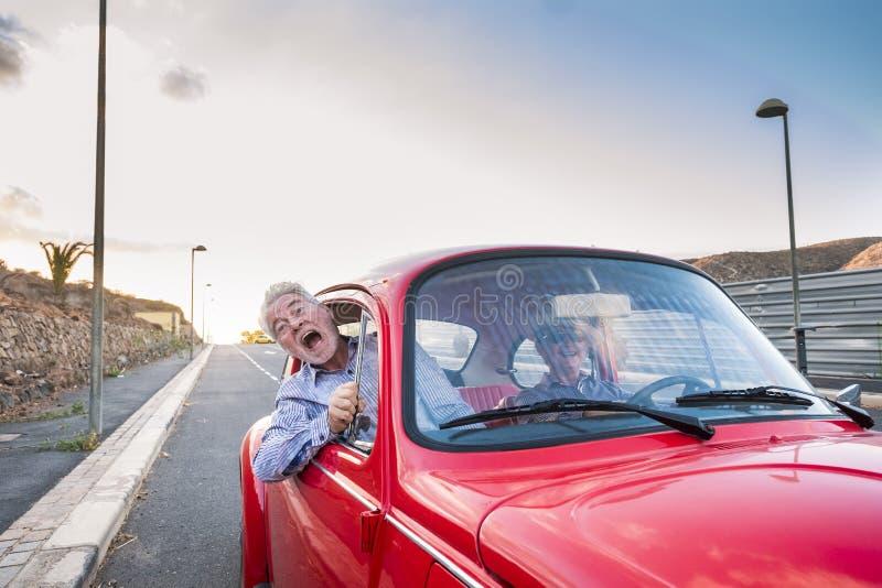Славные красивые старшие взрослые пары путешествуя совместно пока привод женщины и окрик человека для устрашения или для crazines стоковые изображения rf