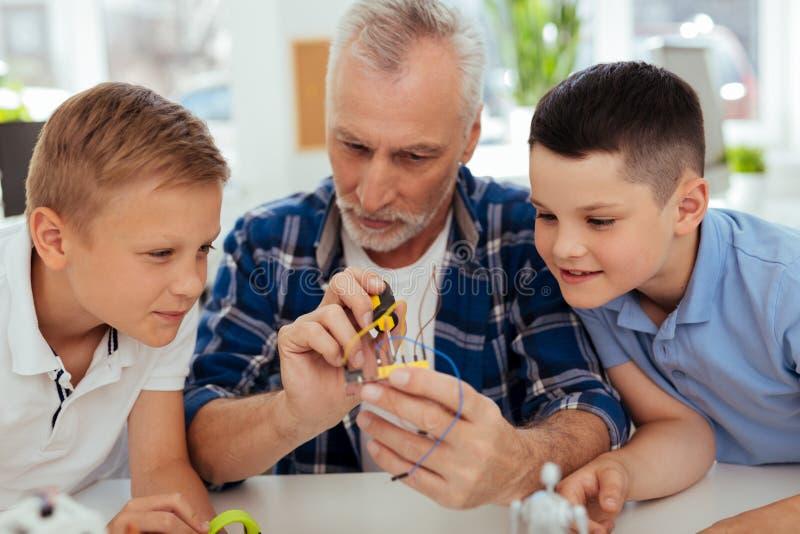 Славные умные дети сидя вокруг их учителя стоковые фото