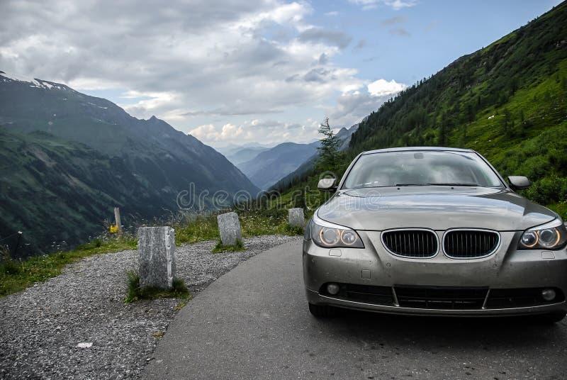 Славный взгляд Альпов за автомобилем стоя на самой высокой отделанной поверхность дороге горы в Австрии - дороге Grossglockner вы стоковая фотография rf