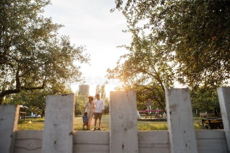 Славный взгляд семьи стоя совместно Они идут в сад Родители смотрят их ребенка стоковая фотография
