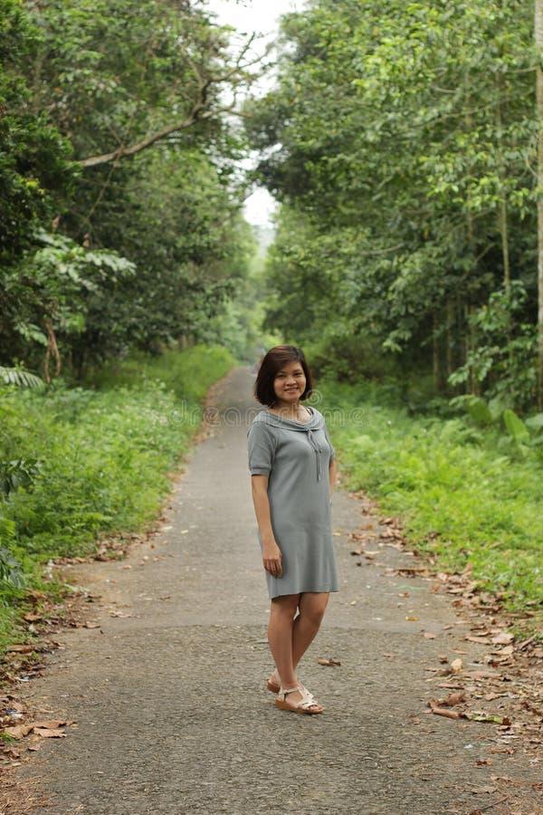 Славный ландшафт со стойкой женщины в лесе и ей очень счастлив стоковое изображение