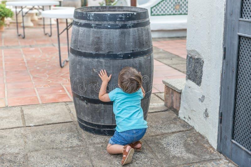 Славный мальчик одетый в голубых играх для скрывания за бочонком стоковое фото
