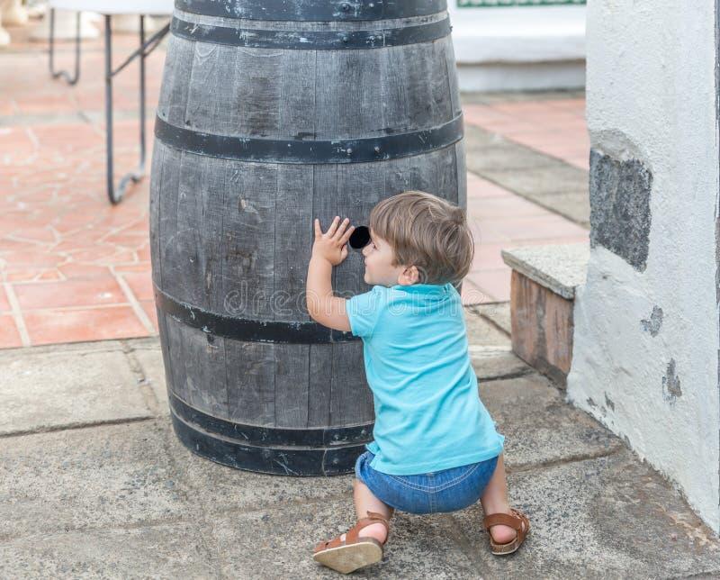 Славный мальчик одетый в голубых играх для скрывания за бочонком стоковые изображения