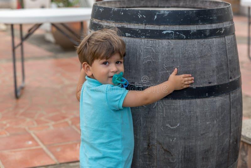 Славный мальчик одетый в сини с объятиями pacifier бочонок стоковые фото