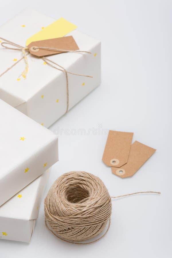 Славный настоящий момент упакованный в белой бумаге с небольшими желтыми звездами на белой предпосылке В оболочке подарок для дня стоковые фотографии rf