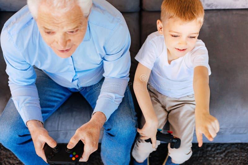 Славный пожилой человек играя видеоигры стоковые фото