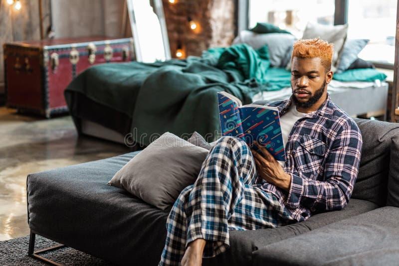 Славный серьезный умный человек читая дома стоковые фотографии rf