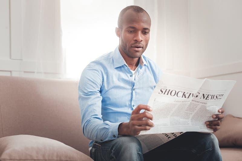 Славный серьезный человек сидя на софе стоковое фото