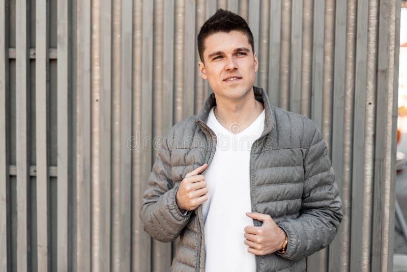 Славный современный молодой человек со стильным стилем причесок в винтажной серой куртке в модной белой стойке футболки около дер стоковые изображения