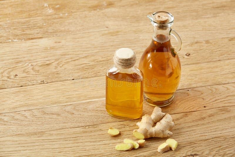 Славный состав 2 опарников масла и имбирь укореняют на деревенской предпосылке, селективном фокусе стоковая фотография