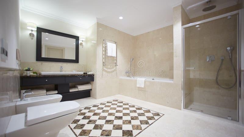 Славный bathroom в современном стиле с серыми крыть черепицей черепицей стенами Белая ванна со стеклянным разделом, ливнем, отраж стоковое изображение rf