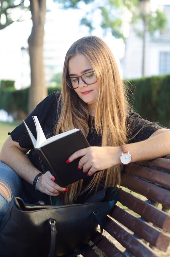 Сладкая белокурая девушка со стеклами читая книгу в скамейке в парке стоковое фото rf