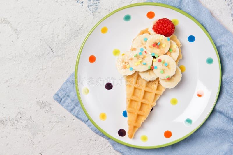 сладкая вафля с бананом и клубникой в форме мороженого конуса, еда для детей идея, вид сверху стоковое фото rf