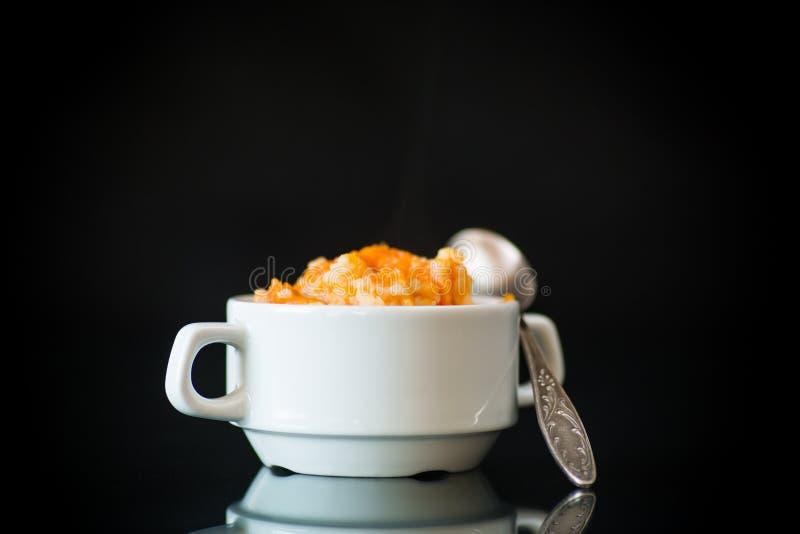 Сладкая кипеть каша тыквы с рисом в плите на черноте стоковое фото