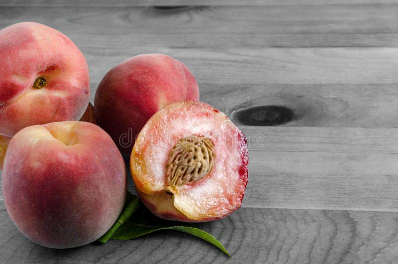 Сладкие персики и зеленые лист на деревянной предпосылке стоковая фотография