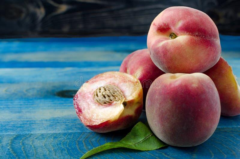 Сладкие персики и зеленые лист на деревянной предпосылке стоковые фотографии rf
