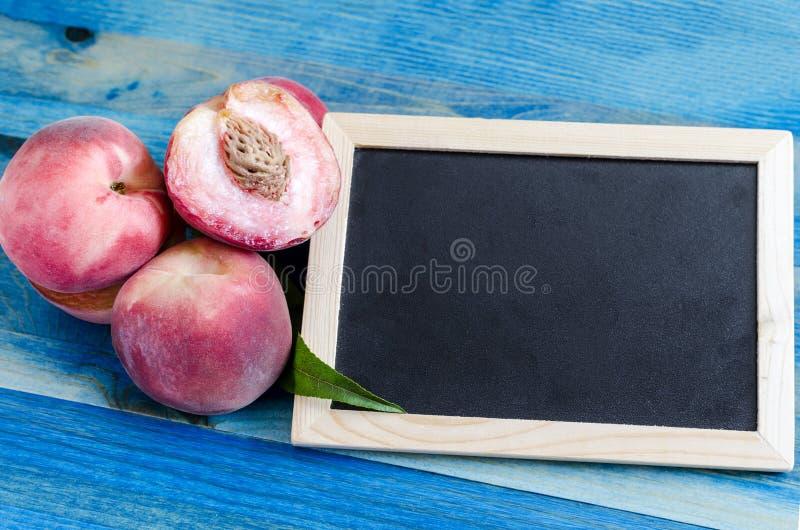 Сладкие персики и зеленые лист на деревянной предпосылке стоковое изображение