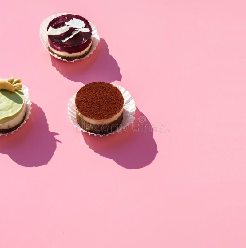 сладкие торты на розовом фоне стоковое изображение