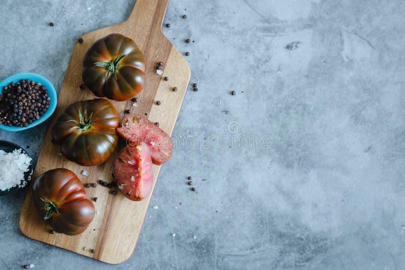 Сладкие целый и отрезок томатов Marmande на деревянной доске и каменной предпосылке r стоковое изображение rf