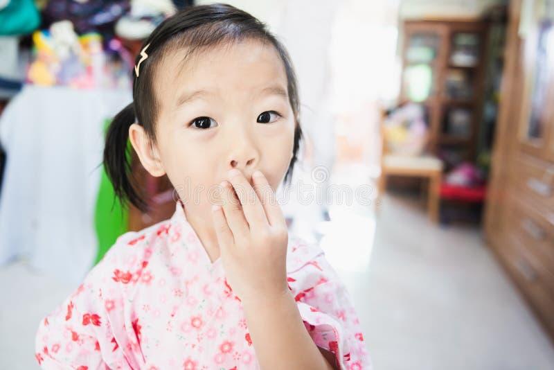 Сладкий азиатский сюрприз маленького ребенка с круглой рукой рта и использования покрывает ее рот стоковые изображения