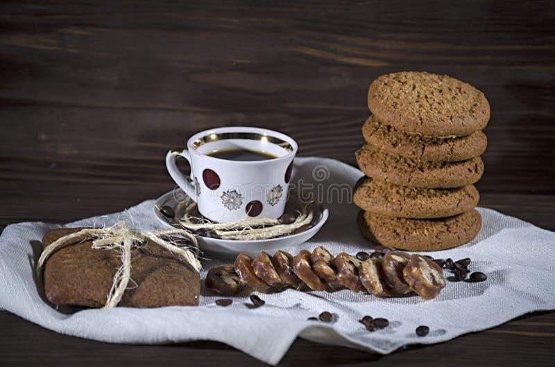Сладкий десерт с кофе, стог печений овсяной каши и пряник на белой скатерти белья, деревянная предпосылка, настроение стоковое изображение rf