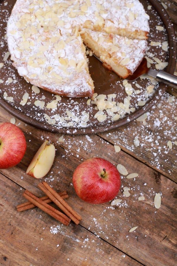 сладкий домашний яблочный торт с корицей и свежими яблоками на заросшем деревянном столе стоковое фото